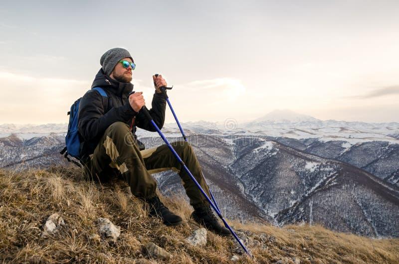 Jonge gebaarde hipster die een hoed en zonnebril met Noordse wandelstokken en een rugzak dragen beweegt zich in de bergen bij stock foto