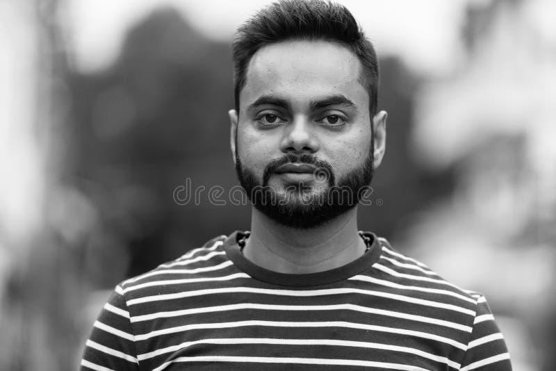 Jonge gebaarde Indische mens in openlucht in zwart-wit stock fotografie