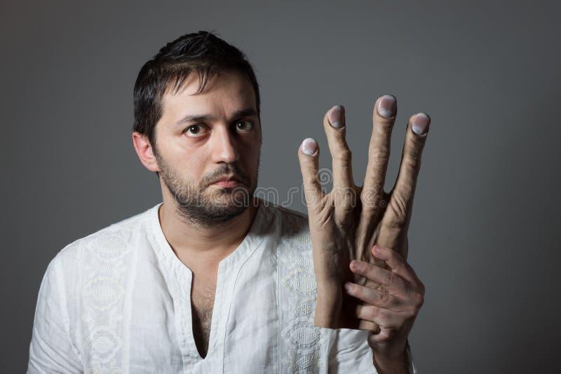 Jonge gebaarde mens die een reusachtige onechte hand houden stock afbeeldingen