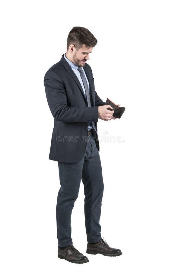 Jonge gebaarde mens die in kostuum binnen zijn lege portefeuille kijken stock foto