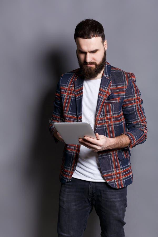 Jonge gebaarde mens die tabletcomputer met behulp van royalty-vrije stock afbeelding