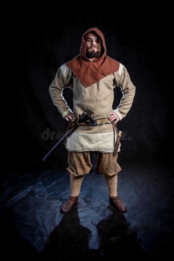 Jonge gebaarde mens in een de leeftijdskleding van Viking en kap met een bijl stock foto's
