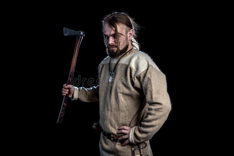 Jonge gebaarde mens in een de leeftijdskleding van Viking met een bijl stock afbeelding