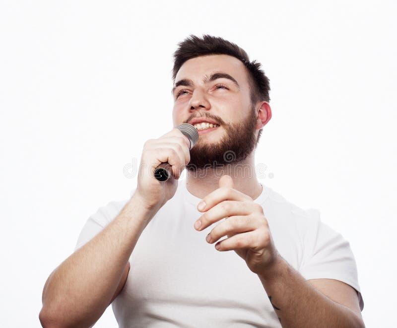 Jonge gebaarde mens in het witte overhemd zingen in microfoon stock fotografie