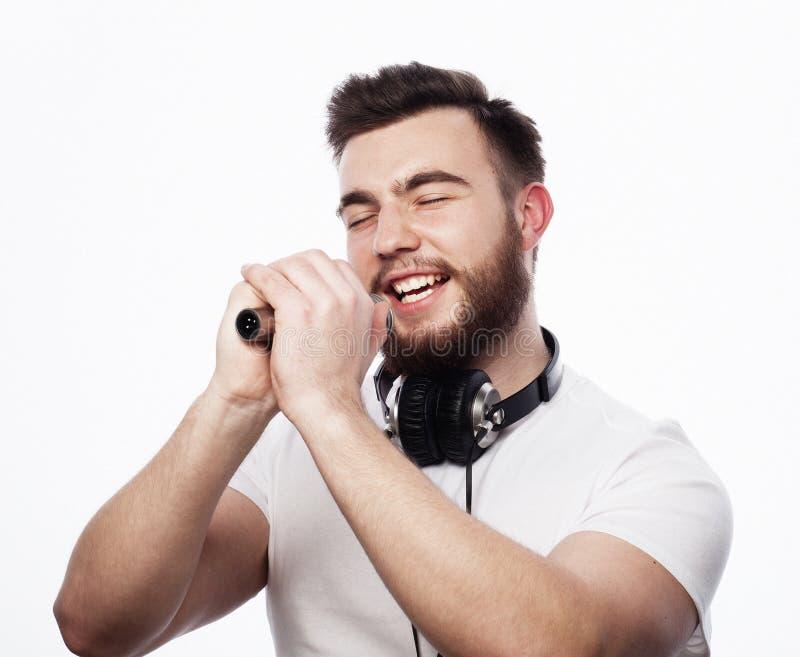 Jonge gebaarde mens in het witte overhemd zingen in microfoon royalty-vrije stock foto
