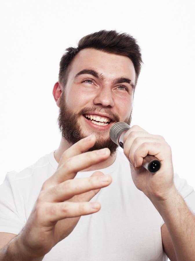 Jonge gebaarde mens in het witte overhemd zingen in microfoon stock afbeeldingen