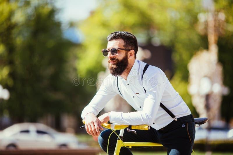 Jonge gebaarde mens hipster in bij zijn fiets leunen en zonnebril die weg terwijl status op stadsstraat eruit zien royalty-vrije stock fotografie