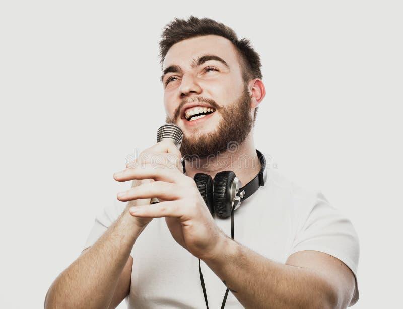 Jonge gebaarde mens met hoofdtelefoons en microfoon over witte achtergrond royalty-vrije stock foto