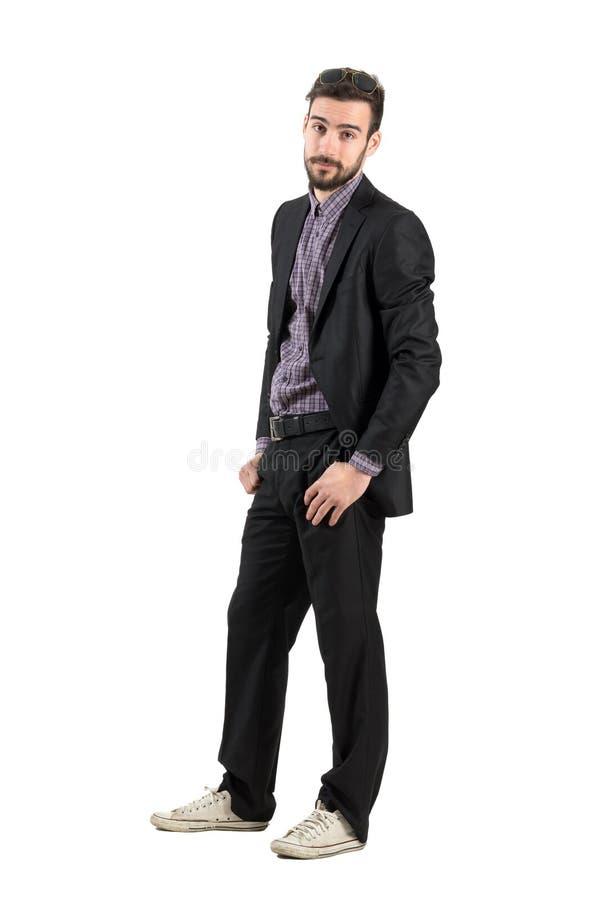Jonge gebaarde mens in onverschillig pak en witte tennisschoenen royalty-vrije stock afbeeldingen