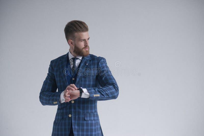 Jonge gebaarde modieuze zakenmanleider die binnen drie-stuk kostuum met horloge dragen die opzij ernstig kijken Ge?soleerd op gri stock afbeelding