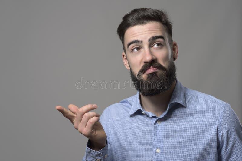 Jonge gebaarde slimme toevallige bedrijfsmens met niet slechte gezichtsgoedkeuringsuitdrukking die vinger richten op copyspace royalty-vrije stock afbeelding