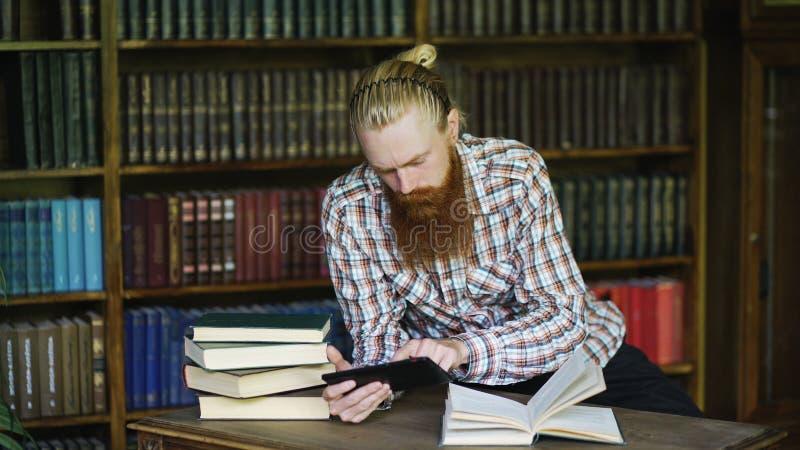 Jonge gebaarde student in bibliotheek die een boek lezen en tabletcomputer op examens met behulp van voor te bereiden royalty-vrije stock foto