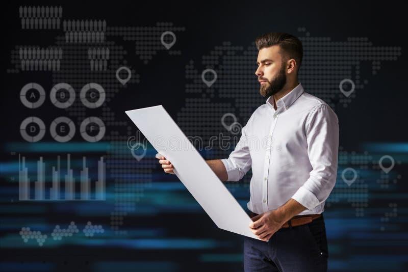 Jonge gebaarde zakenman die en tablet bevinden zich houden Virtuele wereldkaart met pictogrammen van punten, grafiek, diagrammen royalty-vrije stock foto