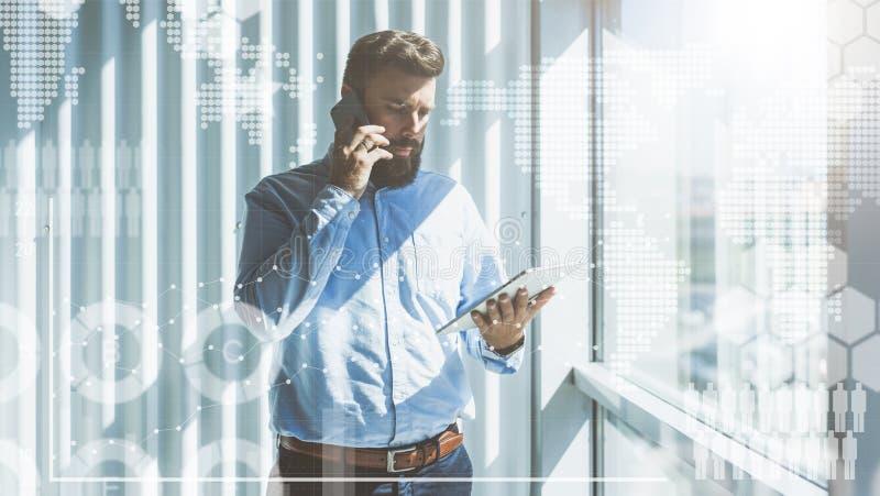 Jonge gebaarde zakenman in overhemd die zich in een bureau dichtbij het venster bevinden en op een celtelefoon spreken terwijl he stock fotografie