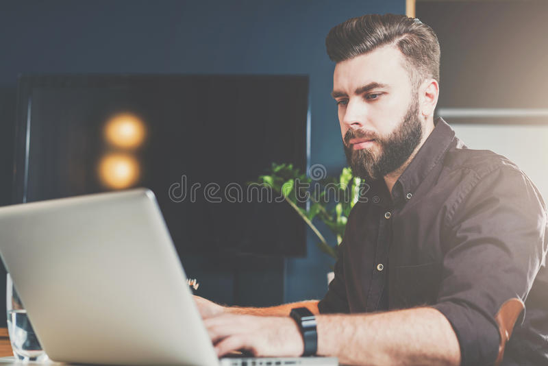 Jonge gebaarde zakenmanzitting in bureau bij lijst en het werken aan laptop Mens blogging, het babbelen, die e-mail controleren stock fotografie