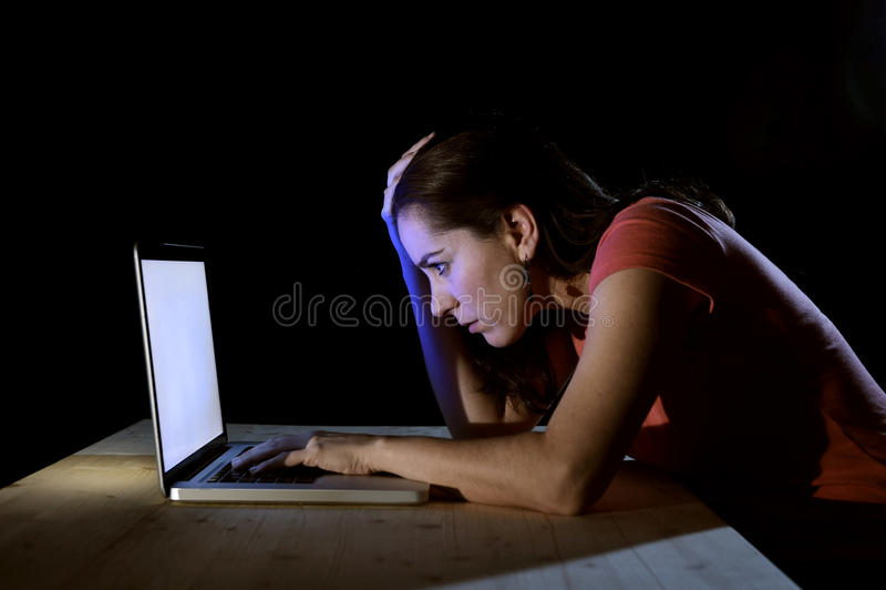 Jonge geconcentreerde freelance arbeider of studentenvrouw die met computerlaptop alleen laat bij nacht in spanning werken die vo stock afbeelding