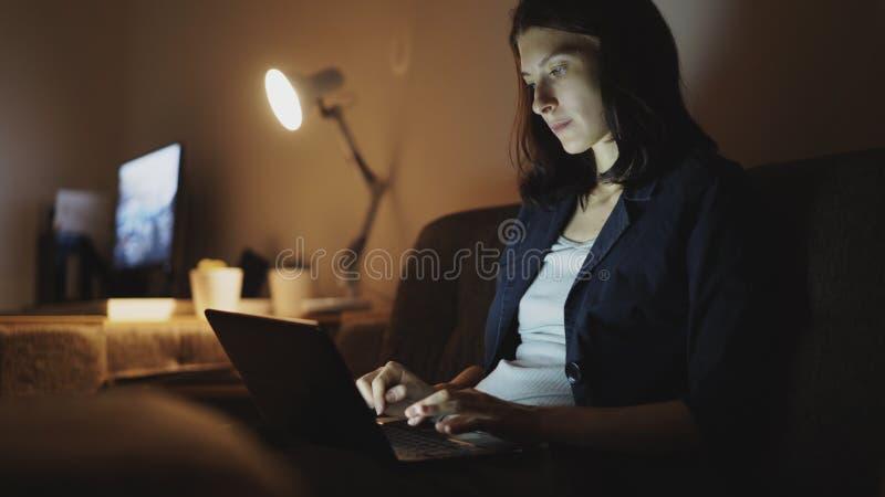 Jonge geconcentreerde vrouw die bij nacht werken gebruikend laptop computer en typend bericht stock fotografie