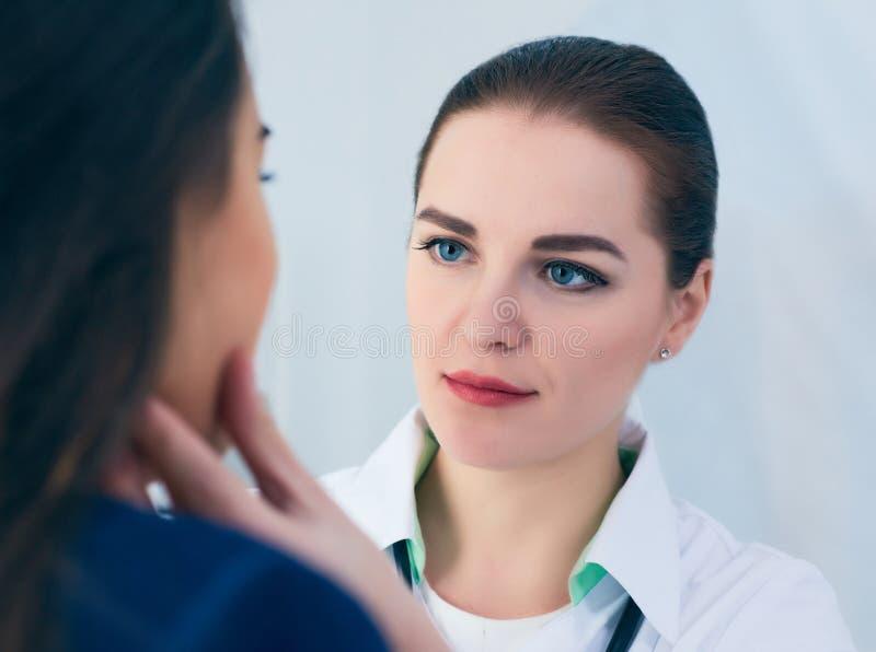 Jonge geconcentreerde vrouwelijke arts die lymfeknopen van een patiënt palperen Arts wat betreft de keel van een patiënt royalty-vrije stock foto's