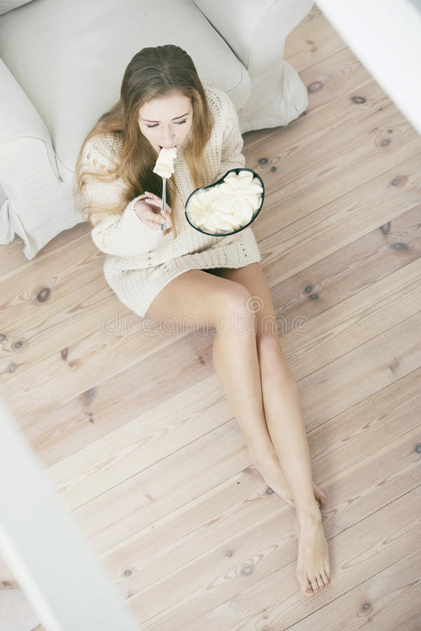 Jonge gedeprimeerde vrouw die roomijs eten royalty-vrije stock afbeeldingen