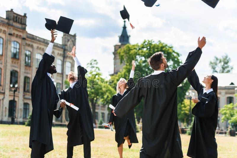 jonge gediplomeerde studenten die op graduatiekappen werpen stock foto's