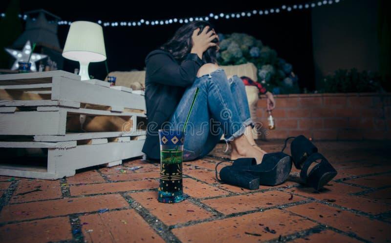 Jonge gedronken vrouwenzitting in de vloer na partij stock afbeelding