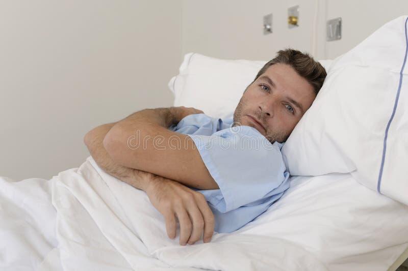 Jonge geduldige mens bij het ziekenhuisbed liggen die het vermoeide droevig kijken rusten en ongerust gemaakt gedeprimeerd die royalty-vrije stock afbeelding