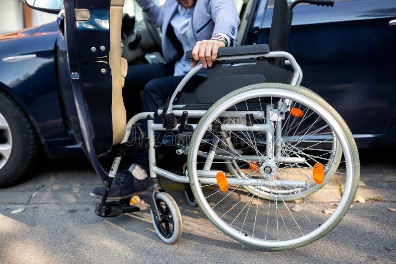 Jonge gehandicapte mens die voor zijn rolstoel bereiken stock foto