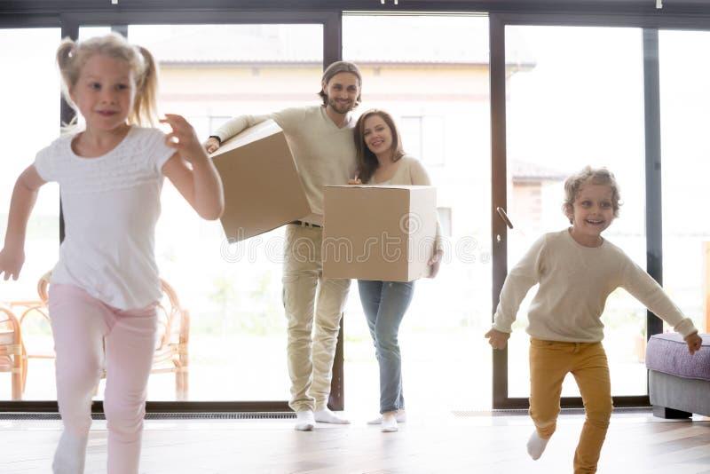 Jonge gehele familie die zich bij nieuw huis bewegen stock afbeelding