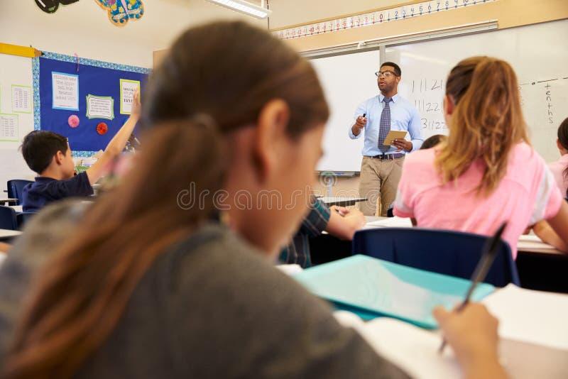 Jonge geitjes die aan leraar tijdens een basisschoolles luisteren royalty-vrije stock fotografie