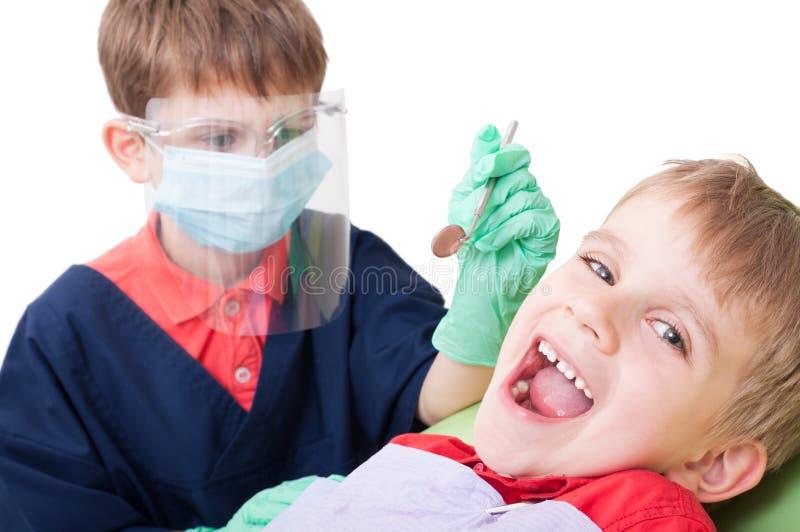 Jonge geitjes die als arts en patiënt spelen stock foto's