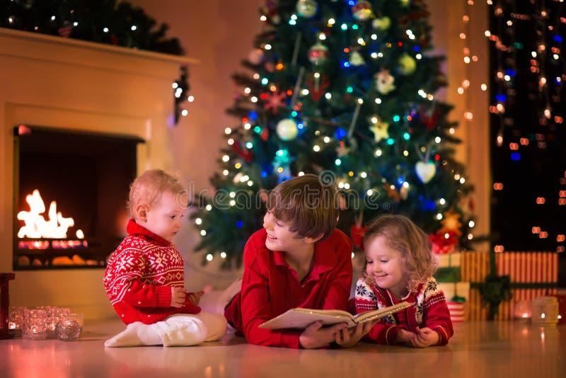 Jonge geitjes die bij open haard op Kerstmisvooravond spelen royalty-vrije stock afbeelding