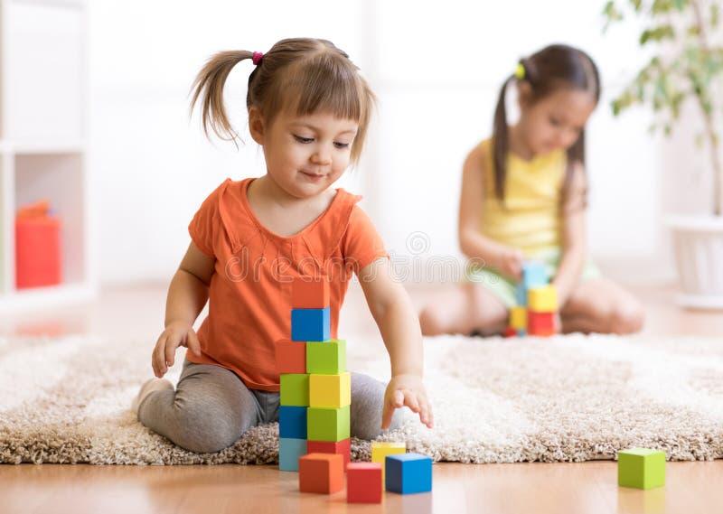 Jonge geitjes die blokspeelgoed in speelkamer spelen bij kinderdagverblijf royalty-vrije stock afbeelding