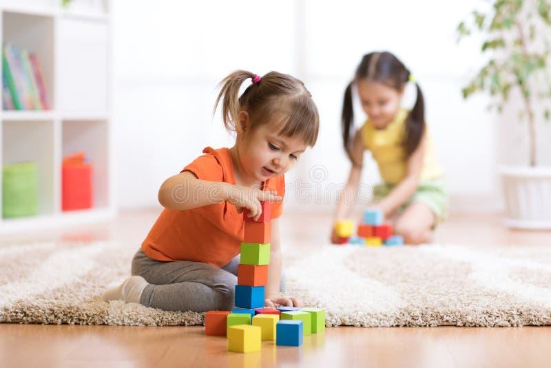 Jonge geitjes die blokspeelgoed in speelkamer spelen bij kinderdagverblijf royalty-vrije stock foto