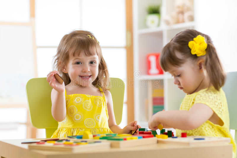Jonge geitjes die blokspeelgoed in speelkamer spelen bij kinderdagverblijf stock foto