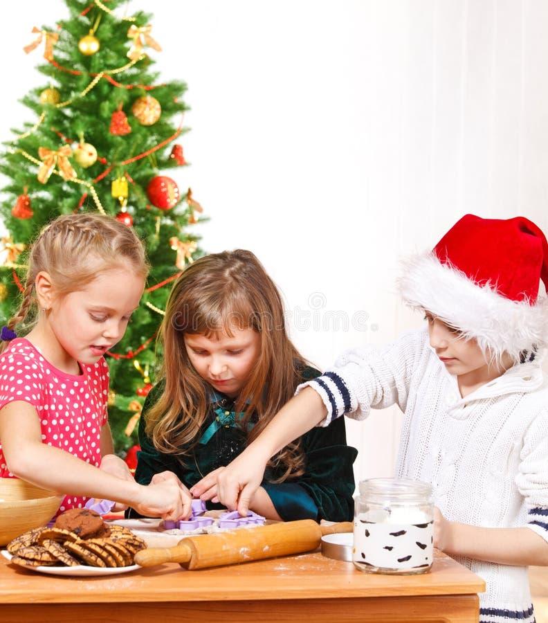 Jonge geitjes die de koekjes van Kerstmis maken stock foto