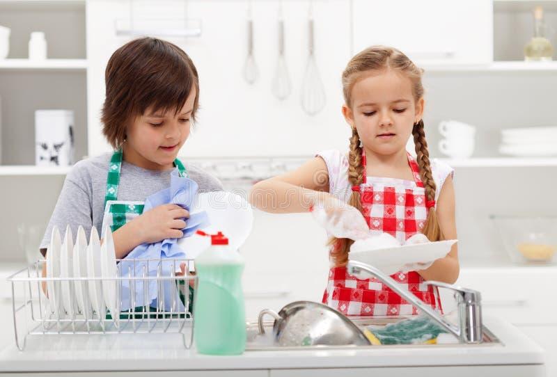 Jonge geitjes die de schotels in de keuken wassen stock afbeelding