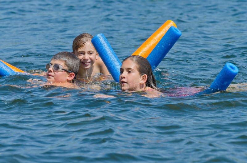 Jonge geitjes die de zomerpret hebben die in meer zwemmen stock afbeeldingen