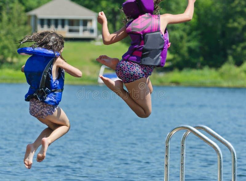 Jonge geitjes die de zomerpret hebben die van dok in meer springen royalty-vrije stock fotografie