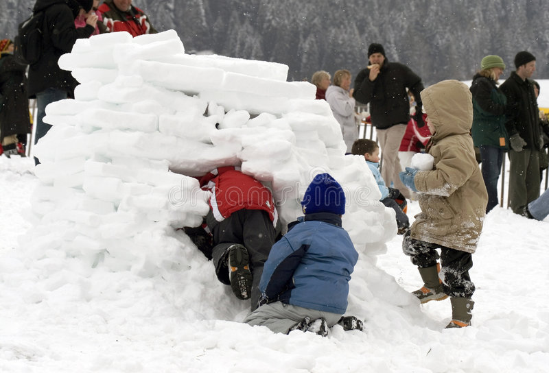 Jonge geitjes die een iglo (sneeuwhuis) bouwen