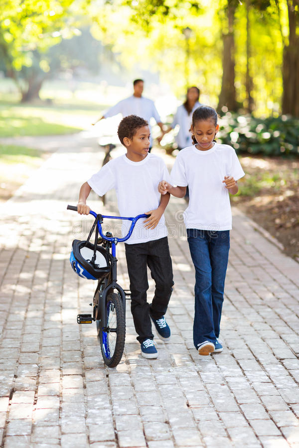 Jonge geitjes die fiets lopen stock foto's