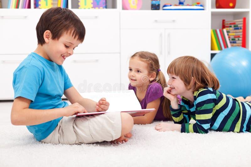 Jonge geitjes die grappig verhaal lezen stock afbeelding