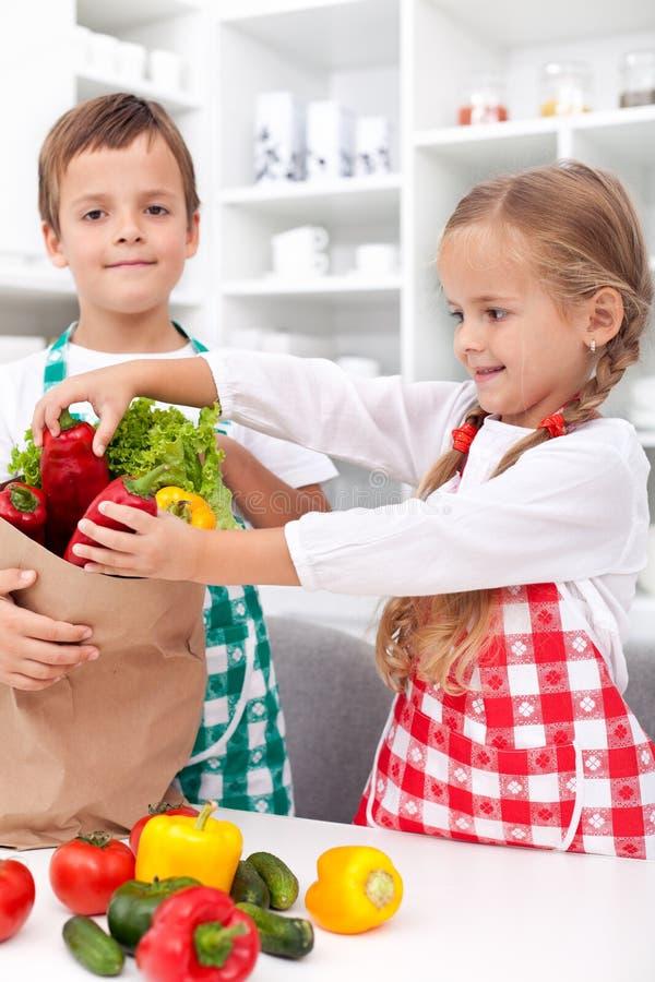 Jonge geitjes die groenten in de keuken uitpakken royalty-vrije stock afbeeldingen