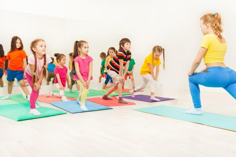 Jonge geitjes die gymnastiek- oefeningen in geschiktheidsklasse doen royalty-vrije stock foto
