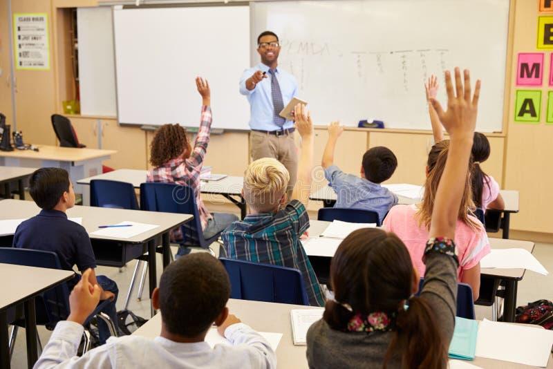 Jonge geitjes die handen opheffen aan antwoord in een basisschoolklasse royalty-vrije stock afbeelding
