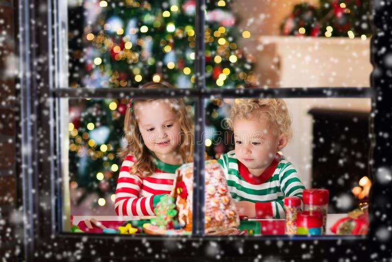 Jonge geitjes die het broodhuis maken van de Kerstmisgember stock foto