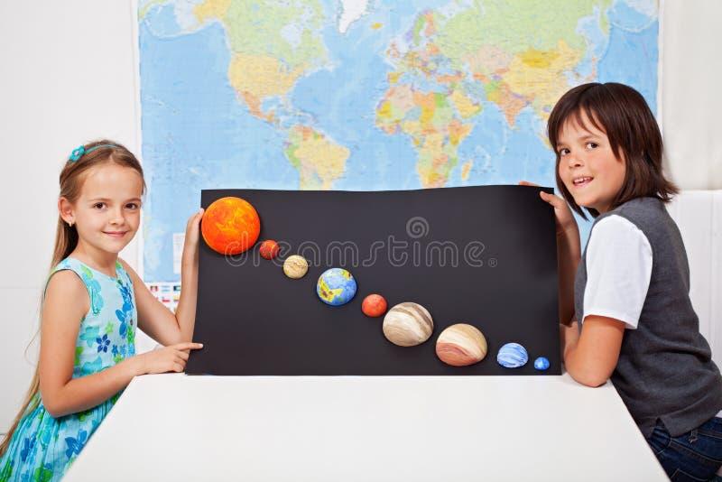 Jonge geitjes die hun project van het wetenschapshuis voorleggen - het zonnestelsel stock afbeeldingen