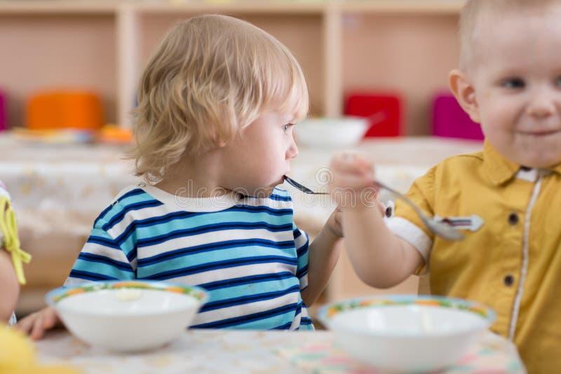 Jonge geitjes die in kleuterschool eten stock afbeeldingen