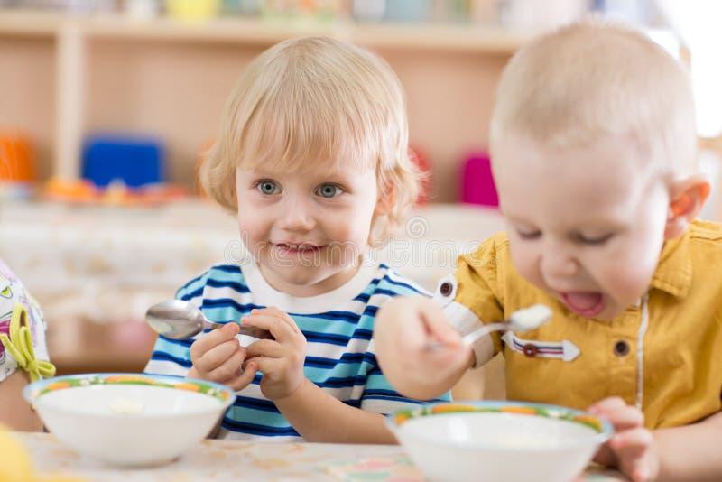 Jonge geitjes die in kleuterschool eten stock foto