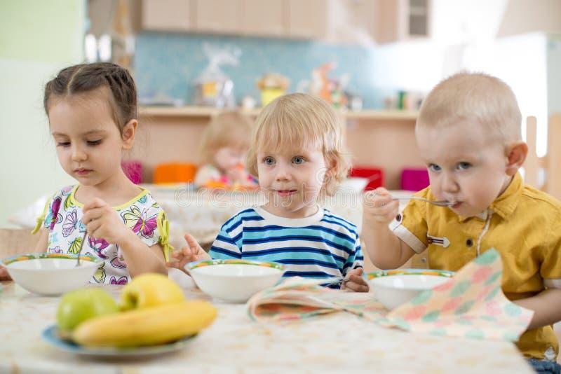 Jonge geitjes die in kleuterschool of opvangcentrum eten royalty-vrije stock afbeeldingen