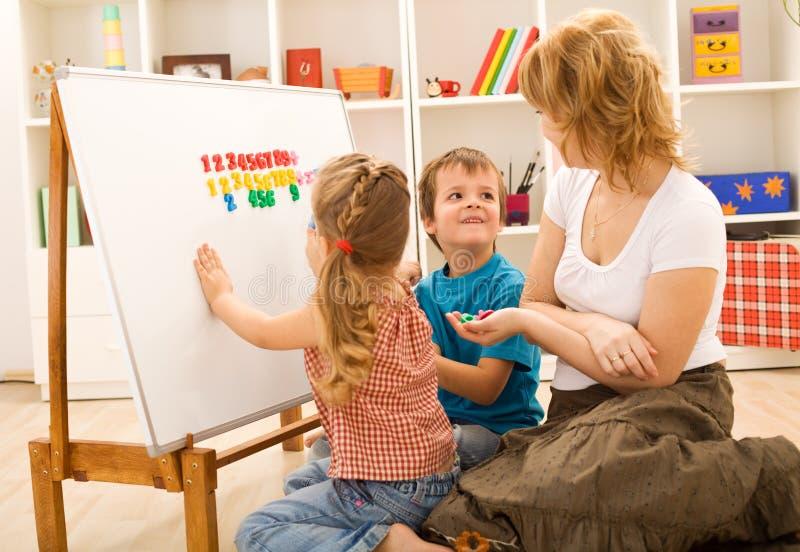 Jonge geitjes die math oefeningen met mamma doen stock afbeeldingen